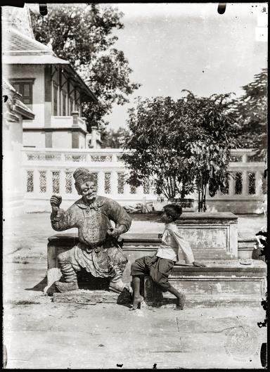 เด็กชายกับตุ๊กตาศิลาจีน ในบริเวณลานพระอุโบสถวัดอรุณราชวรารามด้านทิศเหนือ