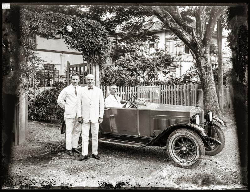 Three European gentlemen with an automobile