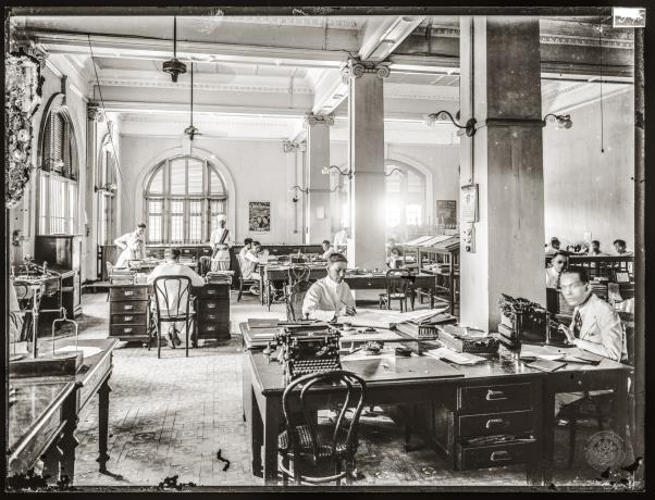 A large open-plan office. Modern features include typewriters